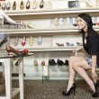 Happy mid adult woman trying high heels in footwear store — Stock Photo