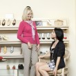 Happy mid adult woman trying on heels while mature female looking in shoe store — Stock Photo