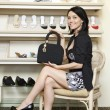 Portrait of a mid adult woman showing designer handbag in footwear store - Stock Photo