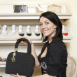 Portrait of a happy mid adult woman showing designer purse in shoe store - Stock Photo