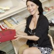 Cheerful mid adult woman with footwear box in shoe store - Foto de Stock