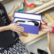 Mid adult woman giving footwear to mature customer in shoe store - ストック写真