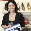 Portrait of a happy mid adult woman with footwear box in shoe store - Foto de Stock