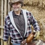 Happy mature cowboy holding saddle — Stock Photo