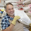 Happy mature salesperson carrying sack in feed store - ストック写真