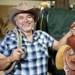 Stock Photo: Happy mature cowboy with saddle and rope in feed store
