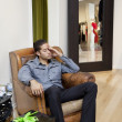 Tired young man sitting on armchair in fashion store - Stock Photo