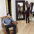 Tired young man sitting on armchair while woman looking at herself in mirror — Stock Photo