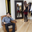 Tired young man sitting on armchair while woman looking at herself in mirror - Stock Photo