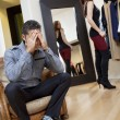 Worried young man sitting on armchair with woman in background trying on clothes - Stock Photo