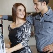 Happy young couple looking at each other while shopping in fashion boutique — Foto de Stock
