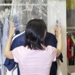 Back view of a mid adult employee putting plastic on dry cleaned clothes — Stock Photo