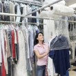 Stock Photo: Happy mid adult woman looking up while putting clothes in plastic