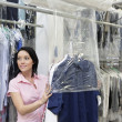Stock Photo: Happy mid adult womlooking away while putting clothes in plastic