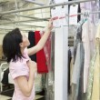 Side view of mid adult woman looking at clothing rack — Stock Photo