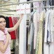 Stock Photo: Portrait of a mid adult woman standing by clothing rack