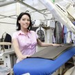 Portrait of a happy mid adult woman standing by ironing machine in laundry — Stock Photo