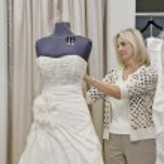 Senior female owner adjusting wedding dress on mannequin in bridal store — Stock Photo #21882811