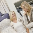 Happy senior mother looking at young daughter in bridal store — Stock Photo #21882883