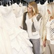 Mother and daughter selecting bridal gown in boutique — Stock Photo #21882943