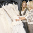 Mother and daughter looking at each other while selecting wedding gown in bridal store — Foto de Stock