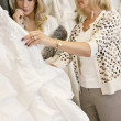 Mother selecting wedding dress for young daughter in bridal store — Stock Photo #21882981