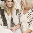Happy mother and daughter looking at each other while selecting wedding dress in bridal boutique — Stock Photo #21883019