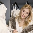 Beautiful young woman looking at price tag of wedding dress in bridal store — Stock Photo #21883021