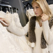 Beautiful blond woman looking at price tag of wedding gown in bridal boutique - Foto de Stock