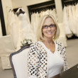 Portrait of happy senior womwearing eyeglasses sitting in bridal store — Stock Photo #21883065
