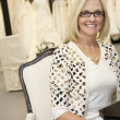Portrait of happy senior female wearing eyeglasses sitting in bridal boutique — Stock Photo #21883087