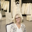 Portrait of happy senior female wearing eyeglasses sitting in bridal store — Stock Photo #21883093
