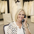 Portrait of a happy woman listening to telephone receiver in bridal store — Stock Photo