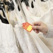 Cropped shot of female hands holding price tag attached to wedding gown in bridal boutique — Stock Photo #21883165