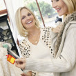 Cheerful mother and daughter looking at price tag of wedding gown in bridal store — Stock Photo #21883183