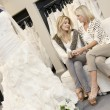 Tilt shot of mother and daughter sitting with footwear in bridal store — Stock Photo #21883195