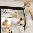 Senior owner assisting young bride getting dressed in wedding gown — Stock Photo #21883347