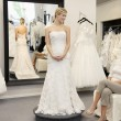 Happy mother looking at young daughter dressed in wedding gown in bridal boutique — Foto Stock