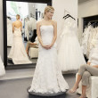 Stock Photo: Happy mother looking at young daughter dressed in wedding gown in bridal boutique