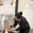 Mature female employee helping bride with footwear in bridal boutique - ストック写真