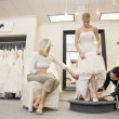 Mother watching as mature employee helping bride with footwear in bridal boutique — Stock Photo #21883415