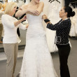 Mother and store employee assisting young woman getting dressed in bridal store - ストック写真