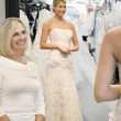 Happy mother admiring daughter dressed in a wedding gown — Stock Photo