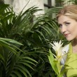 Portrait of a young woman smelling flower in garden center — Stock Photo