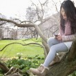 Stock Photo: Young womsitting on tree branch while text messaging