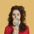 Portrait of a young woman holding lollipop in front of face over colored background — Stock Photo