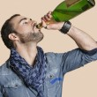 Young man drinking champagne from bottle over colored background — Stockfoto