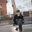 Young businessman working on laptop while sitting on bench — Stock Photo