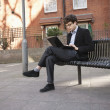 Young businessman using laptop while sitting on bench — Foto Stock