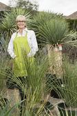 Saksı bitkiler tarafından çevrelenmiş üst düzey kadın bahçıvan portresi — Stok fotoğraf